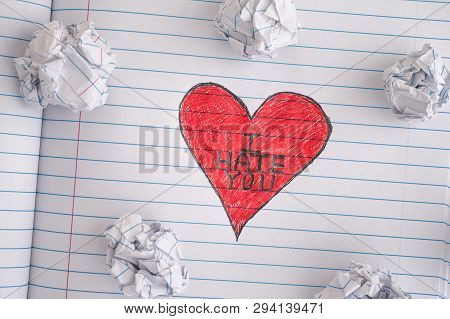 I Hate You. Red Heart With Phrase I Hate You On Notebook Sheet With Some Crumpled Paper Balls On It.