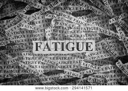 Fatigue. Torn Pieces Of Paper With The Word Fatigue. Concept Image. Black And White. Closeup.