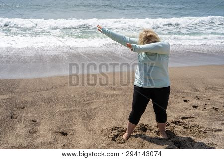 Blonde Woman Does A Dabbing Dance Move On The Beach