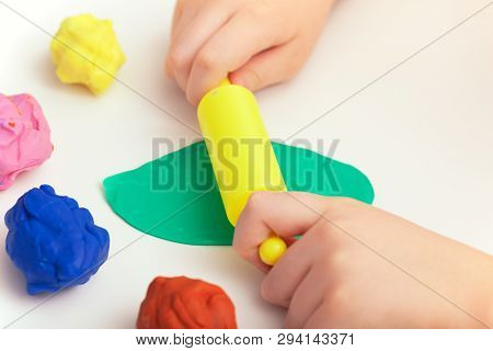 Child Playing Colorful Playdough On A Table. Close Up.