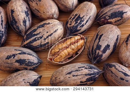Organic Pecan Nuts On A Wooden Table. Close Up