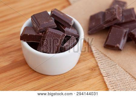 Broken Dark Chocolate Pieces In A Bowl. Close Up.