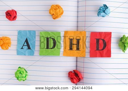 Adhd. Abbreviation Adhd On Notebook Sheet With Some Colorful Crumpled Paper Balls Around It. Close U