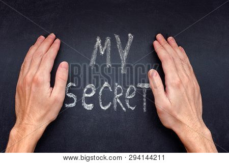Hands Covering Up Words My Secret On A Chalkboard.