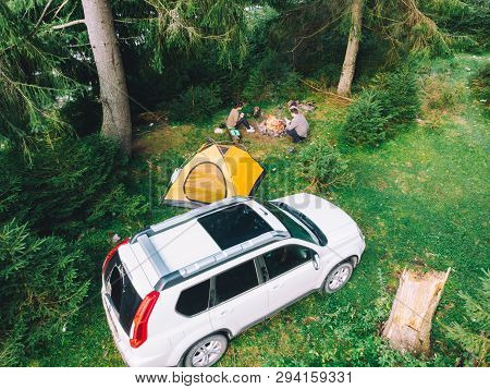 Couple Sitting Near Campfire Drinking Tea. Yellow Tent And White Suv Car. Active Leisure Time