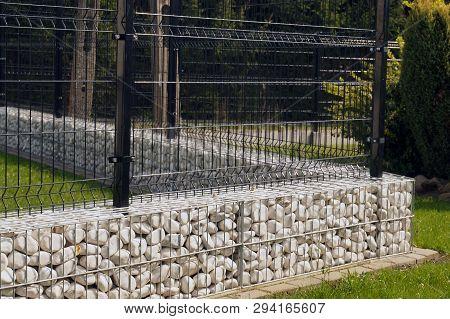A Low Foundation Under A Steel Openwork Fence. Gabion.