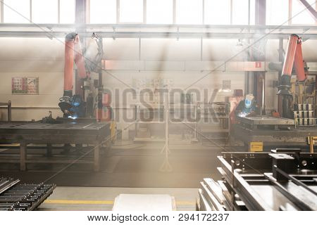 Two contemporary welders in uniform and protective workwear doing welding work inside backlit factory