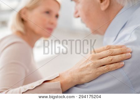 Hand of supportive mature female on shoulder of grieving man as an expression of acceptance and empathy