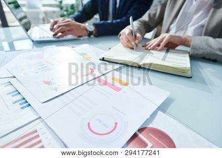 Young contemporary analyst with pen making notes in notebook while analyzing financial papers with colleague typing near by