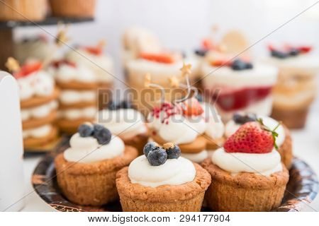 Cake With Various Berries And Meringues On A Stand.cakes, Dessert With Berries, Candy Bar For Party.