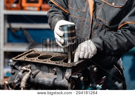 Car Mechanic Holding A New Piston For The Engine, Overhaul.. Engine On A Repair Stand With Piston An