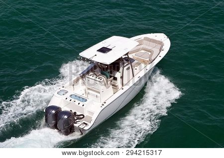 Angled Overhead View Of An Open White Sport Fishing Boat Powered By Two Outboard Engines Cruising On