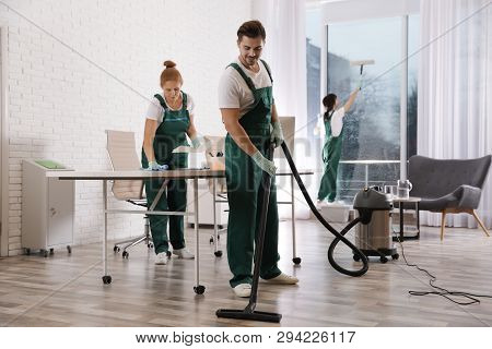 Team Of Professional Janitors Working In Modern Office. Cleaning Service