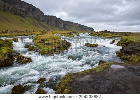 Stormy Mountain River With Rapids And Green Islets In The Middle. Against The Backdrop Of Mountains