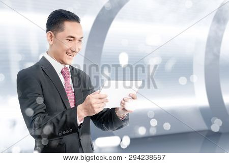 Young Asian Businessman Holding Digital Tablet With His Hand. Future Technology Concept