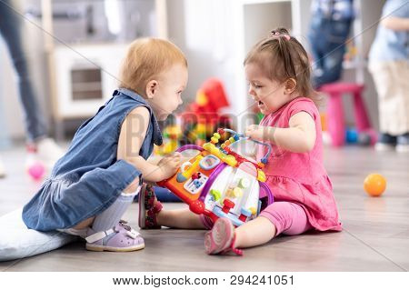 Conflict On The Playground. Two Kids Fighting Over A Toy In Kindergarten Or Nursery