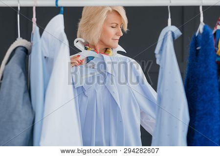Senior Business Lady. Modern Woman Lifestyle. Aged Fashion Trendsetter At Showroom Choosing Outfit F