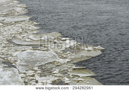 Edge of the ice field and the sludge on the brownish river poster