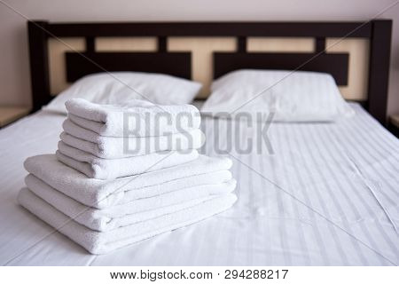 Stack Of White Clean Bath Towels On Bed Sheet In Modern Hotel Bedroom Interior, Copy Space