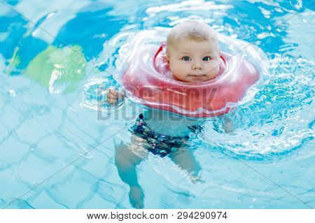 Cute Little Baby Child Learning To Swim With Swimming Ring In An Indoor Pool. Newborn Girl Or Boy Ha