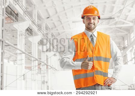 The Builder In A Construction Vest And Orange Helmet Smiling With Sign Ok Against Industrial Backgro