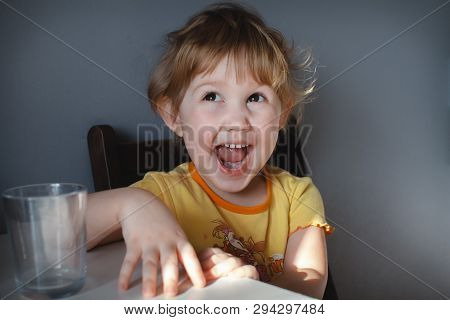 Portrait Of A Funny Child On A Gray Background At The Table Close-up. Funny Antics