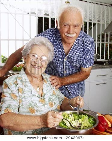 Happy senior couple preparing vegetable salad in the kitchen. Grandparents at kitchen preparing vegetable salad.