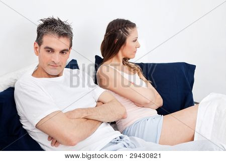 Couple with problems remaing silent with arms crossed in bed