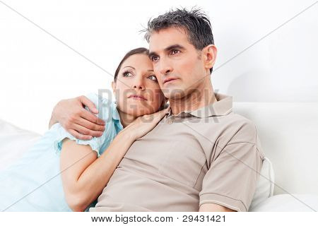 Pensive senior couple thinking on couch at home
