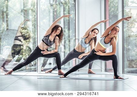 Group Smiling Yoga Women Doing Exercise In Gym. Yoga Team In Gym Class. Young Girls, Sport, Training