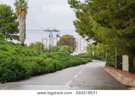 Perspective view of the road on Montjuic mountain, Montjuic Cable Car and Barcelona city from a height in overcast day, Spain poster