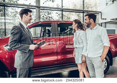 Attractive Couple Is Talking To Car Sales Manager In Luxury Car Dealership And Looking At Beautiful