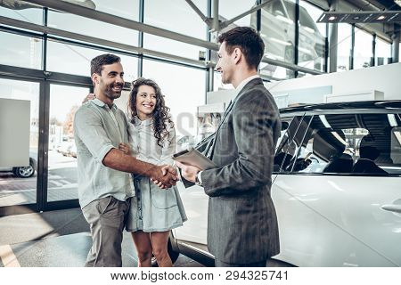 Car Showroom. Young Couple Is Meeting With Seller In Auto Salon.