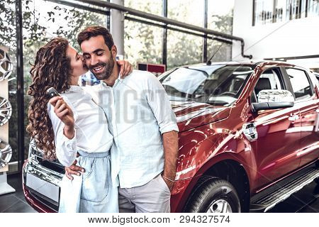 Visiting Car Dealership. Beautiful Couple Is Holding A Key Of Their New Car And Smiling, Girl Is Kis