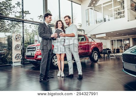 Online Payment. Beautiful Happy Couple Buying A Car At Car Salon Showroom Handsome Car Salesman Show