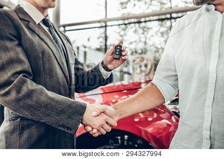 Auto Business, Car Sale, Deal, Gesture And People Concept - Close Up View Of Dealer Giving Key To Ne