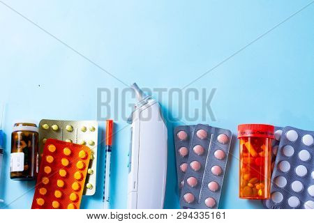 Healthcare Concept - Pills And Medical Thermometr Boder On Plain Blue Background