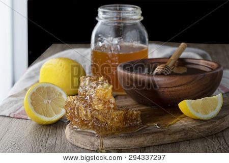Honey In Jar With Honeycomb And Wooden Drizzler With Lemon On Wooden Table. Dark Background