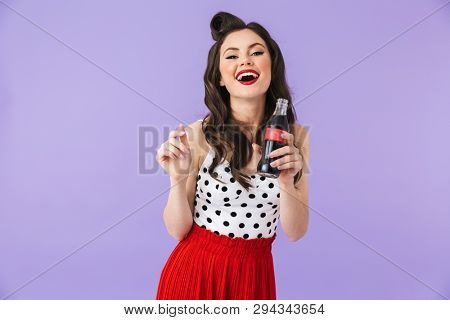 728cefc13 Photo of young pin-up woman 20s in vintage polka dot dress rejoicing while  holding