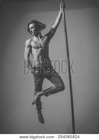 Guy Makes Figure On Pole, Fly In Air. Work Out Concept. Attractive, Sexy Man With Long Hair And Nude