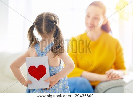Happy mother's day! Child daughter is congratulating mom and giving her card. Mum and girl smiling. Family holiday and togetherness.