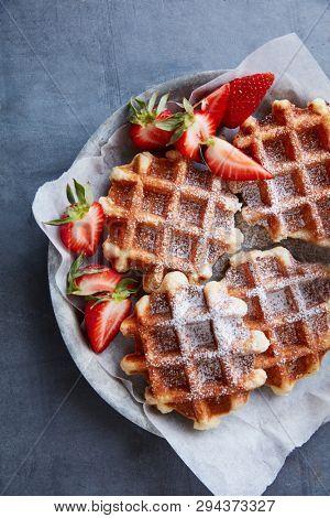 Fresh sugar waffles with castor sugar and strawberries