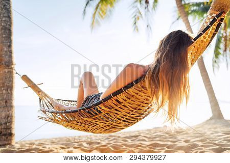 Blonde Longhaired Woman Relaxing In Hammock Hinged Between Palm Trees On The Sand Beach