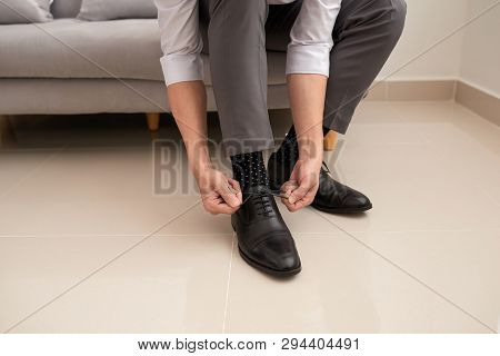 Man's Hands Tying Shoelace Of His New Shoes. People, Business, Fashion And Footwear Concept - Close
