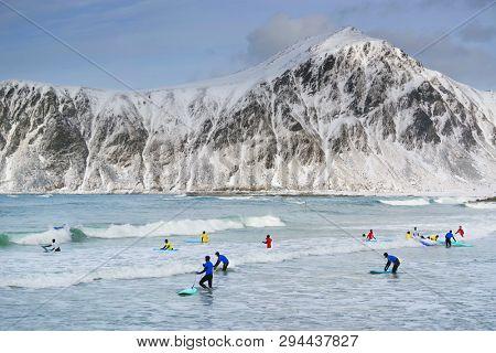 FLAKSTAD BEACH, LOFOTEN ARCHIPELAGO, 26 MARCH, 2019: Young men surfing in arctic conditions at Flakstag Beach, Lofoten, Norway, Europe