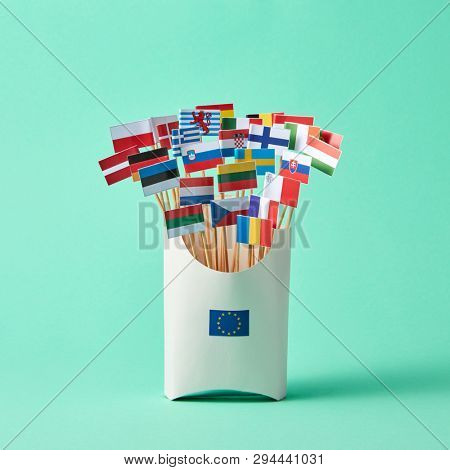 In a cardboard box with sign of the European Union, collection of paper flags of European Union countries on green background . Economic, Political Union of European States