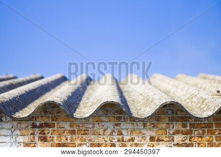 Dangerous Asbestos Roof Over A Brick Wall - One Of The Most Dangerous Materials In The Construction