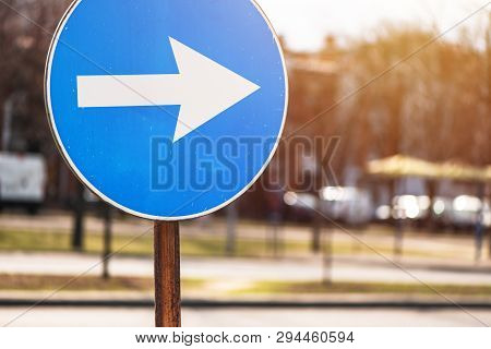 Proceed In Direction Arrow Traffic Sign On The Street With Defocussed Background