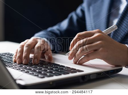 Man In Business Suit Sitting At Desk And Working At Laptop Computer. Close-up Of Human Hands Holding
