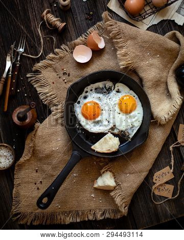 Overhead Shot Of Cast-iron Pan With Two Fried Eggs And Bread On Sackcloth Standing On Wooden Rustic